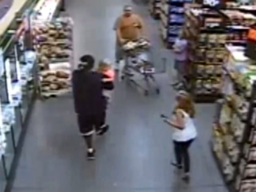 The scene in the store as Wallace walks away holding Zoey, captured on surveillance video.