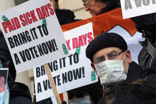 FILE- In this Friday, Jan. 18 2013 file photo, activists hold signs during a rally at New York's City Hall to call for immediate action on paid sick d...