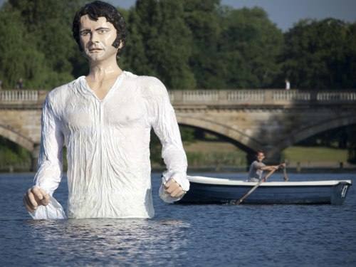 A passerby takes a look at the 12-foot Mr. Darcy.