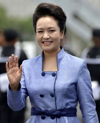 Chinese First Lady Peng Liyuan, wife of Chinese President Xi Jinping, waves at the reception committee upon their arrival at the airport on June 4, 20...