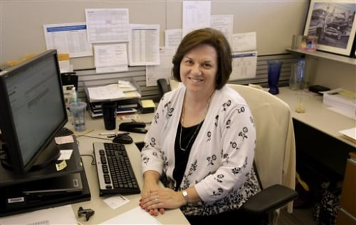 In this June 3, 2013, photo, Nora Kouba, an employee at USG Corporation sits at her work station in Chicago. Over the years, Kouba has made use of a b...