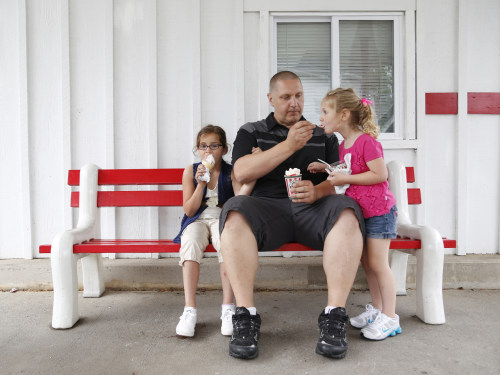 Carl Poff feeds his daughter Joselyn, 4, a bite of ice cream outside Rita's Italian Ice in Easton, Pa.