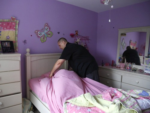 Carl Poff of Easton, Pa., makes one of his daughter's beds on Thursday, June 14, 2013. Part of Poff's daily routine is to make beds and clean up the h...