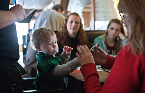 Shelly Sachwitz hands  an iPhone with a game on the screen to  her one-year-old grandson Lucas.