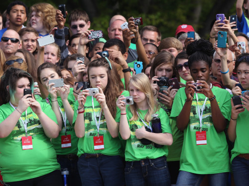 Young girls take pictures as they wait for Prince Harry to arrive at Arlington National Cemetery.