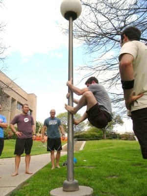 MovNat Workshop participants in Orlando practice a foot-pinch climb using a lamp post
