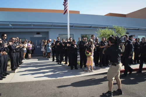 Phoenix Police Department officer with 5-year-old Tatum, her mother, Stephanie Raetz, on the morning of the girl's graduation from kindergarten.