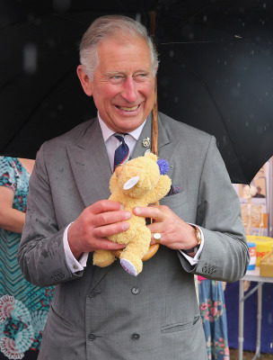 KING'S LYNN, ENGLAND - JULY 31:  Prince Charles, Prince of Wales is presented with a teddy bear for Prince George of Cambridge during a visit to the 1...