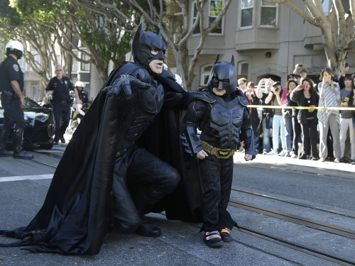 Miles, dressed as Batkid, right, walks with Batman before saving a damsel in distress in San Francisco.