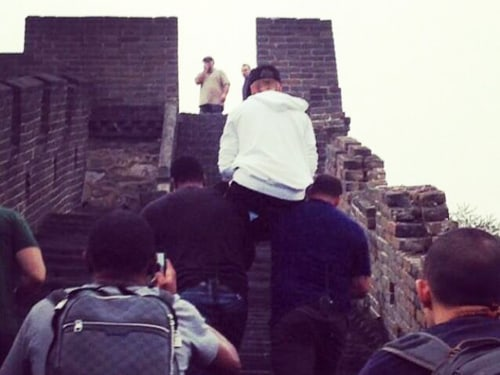Justin Bieber gets a little help from his friends while on the Great Wall of China.