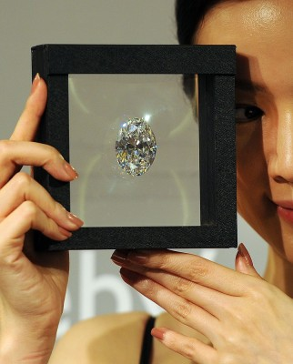 In this picture taken on September 19, 2013 a model holds a flawless oval diamond during a media preview at Sotheby's auction house in Hong Kong. The ...