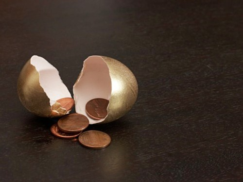 Cracked golden egg containing pennies