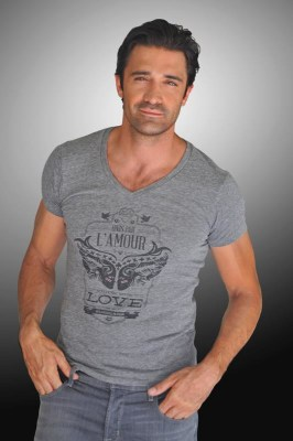 Giles Marini poses in a T-shirt that supports research for breast cancer.