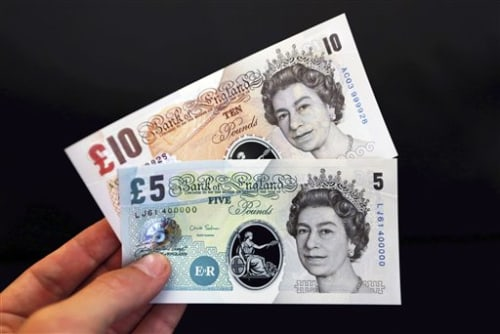 A sample the proposed new British banknotes made of a polymer, five pound and ten pound notes held for an arranged photograph during a news conference...