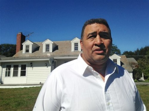 Former NFL offensive lineman Brian Holloway stands in front of his rural vacation home Wednesday, Sept. 18, 2013, in Stephentown, N.Y. Holloway's rura...