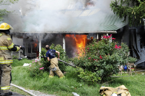 Firefighters from several Henderson County volunteer fire departments battle a house fire at 6877 Old Henderson-Spottsville Road in Spottsville, Ky. o...