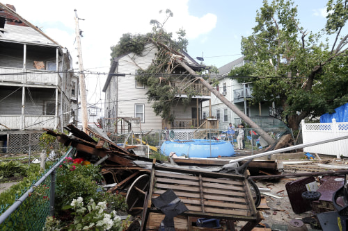 People observe the damage in the back of several houses in Revere, Mass. Monday, July 28, 2014, after a tornado touched down. Revere Deputy Fire Chief...