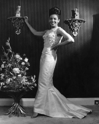 December 1962:  Popular Welsh singer Shirley Bassey tries on another dress during her quest for what to wear to the White House, where she has been as...