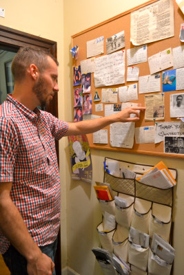 "Sean Gibbons, 28, checks out the communal bulletin board at his shared rental in Seattle. So many people are interested in living there that the group has an occasional ""open house"" to select new roommates from among applicants."