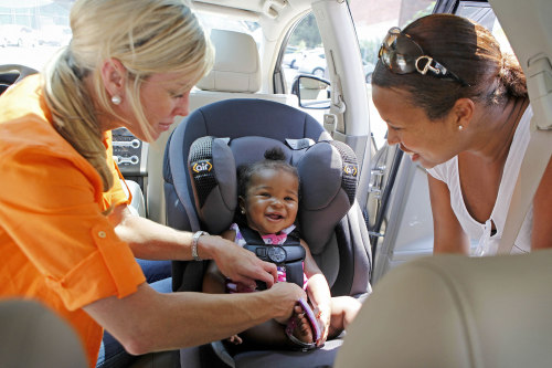 Child Safety Expert Kimberlee Mitchell, left, installs a car seat for Kennedy Word, 8 months, as mother Kimberly St. Louis looks on during a car seat ...
