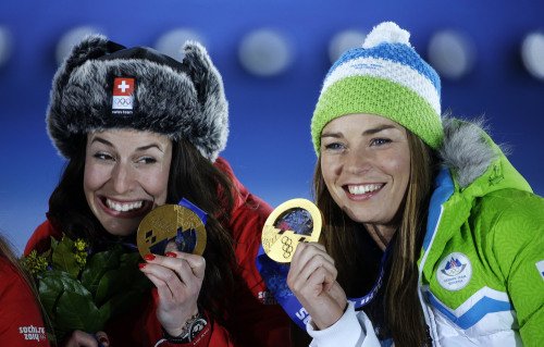 Dominique Gisin of Switzerland, left, and Tina Maze of Slovenia, right, who tied for the gold medal in the women's downhill  pose during their medals ...