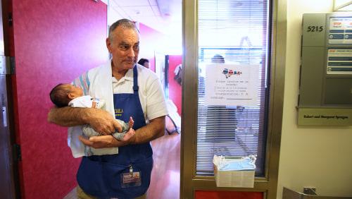 LOS ANGELES, CA - DECEMBER 11, 2013:  Volunteer Jim O'Connor walks around the hospital with month-old patient Mace De Luna at Children's Hospital Dece...