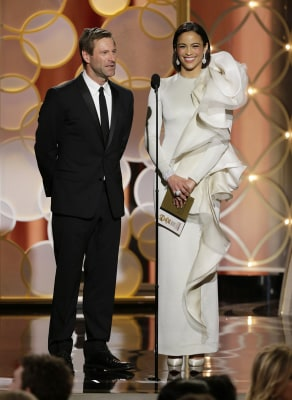 This image released by NBC shows presenters Aaron Eckhart and Paula Patton during the 71st annual Golden Globe Awards at the Beverly Hilton Hotel on S...