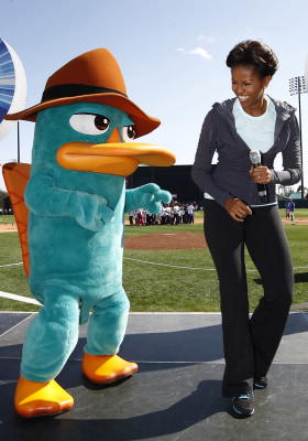 "U.S. First Lady Michelle Obama laughs next to Perry the Platypus from the children's TV show ""Phineas and Ferb"", during a ""Let's Move!"" faith and comm..."