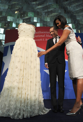 US First Lady Michelle Obama (R) touches her 2009 inaugural gown as the designer of Mrs. Obama's inaugural dress, Jason Wu, looks on during a ceremo...