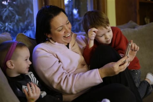 Julie Young, a Boston-based behavioral analyst, center, sits with her sons Nolan, 3, left, and Jameson, 4, right, while looking at a smart phone at th...