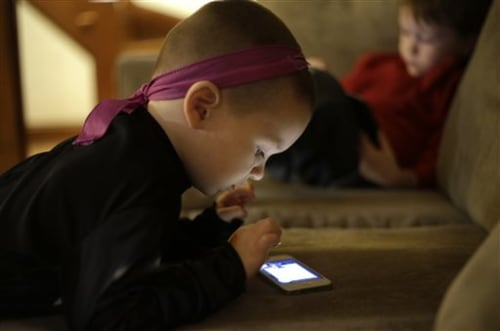 Nolan Young, 3, front, looks at a smart phone while his brother Jameson, right, 4, looks at a smart tablet at their home, in Boston, Monday, Jan. 27, ...