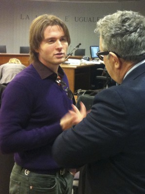 Raffaele Sollecito talks with an unidentified man prior to the start of the final hearing before the third court verdict for the murder of British stu...