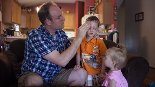 Corey Fontenot's daughter, Cora, 16 months, looks on as her father applies sunscreen to son Isaac's face.