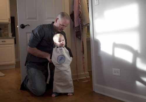 Juip puts an apron on his son Ari while making dinner at their home.