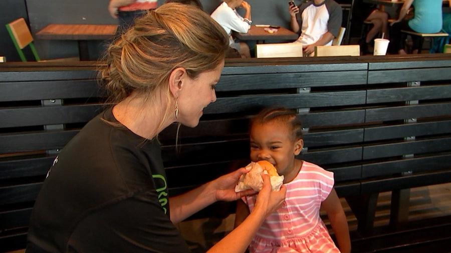 Natalie Morales (and little helper) promote Al's Roker Burger at Shake Shack