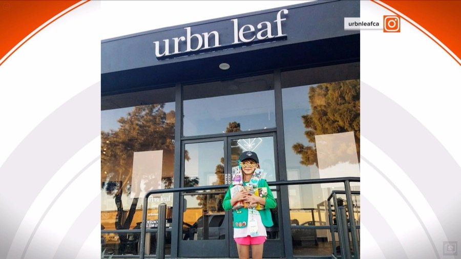 Girl selling girl scout cookies in front of marijuana dispensary