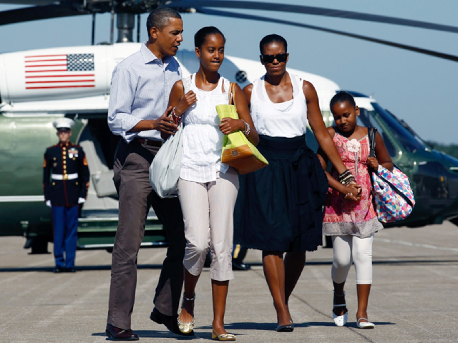 Image: U.S. President Obama walks to Air Force One with first lady Michelle and their daughters Sasha and Malia at Cape Cod Coast Guard Air Station in Bourne