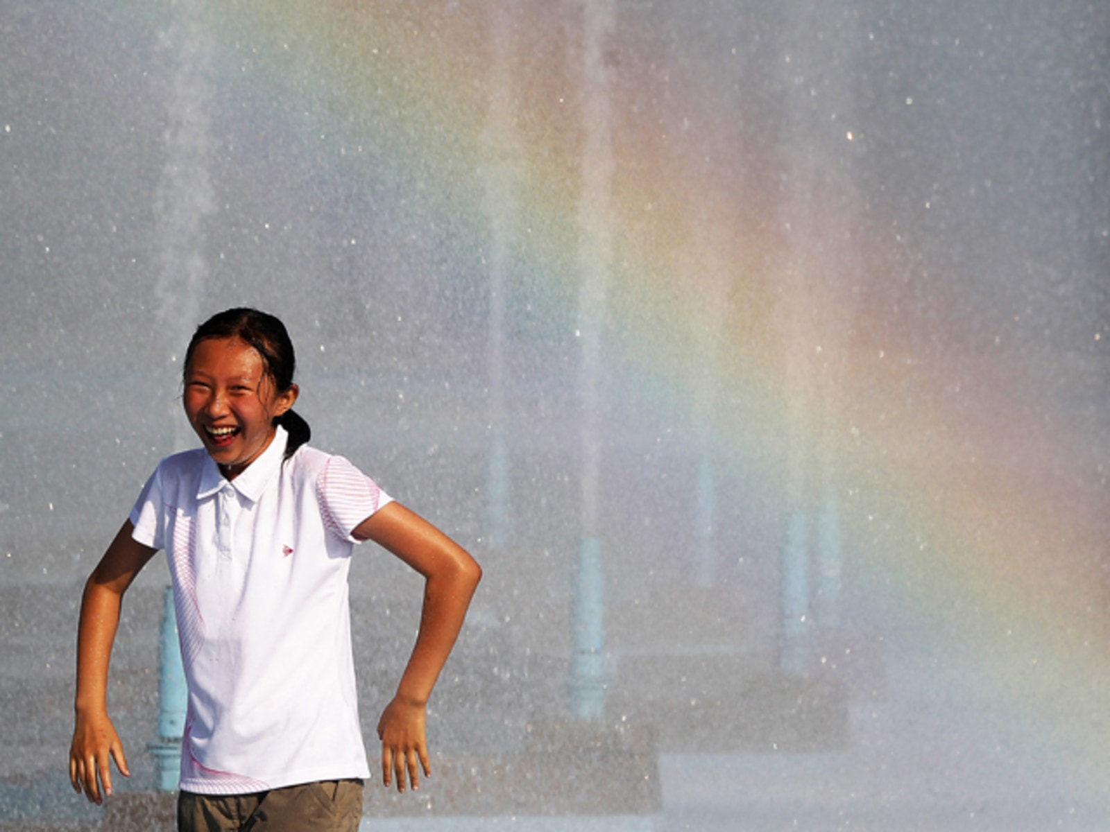 Image: A girl cools off in the Unisphere fountain at the Flushing Meadows-Corona Park as a rainbow streaks across the water in the Queens borough of New York