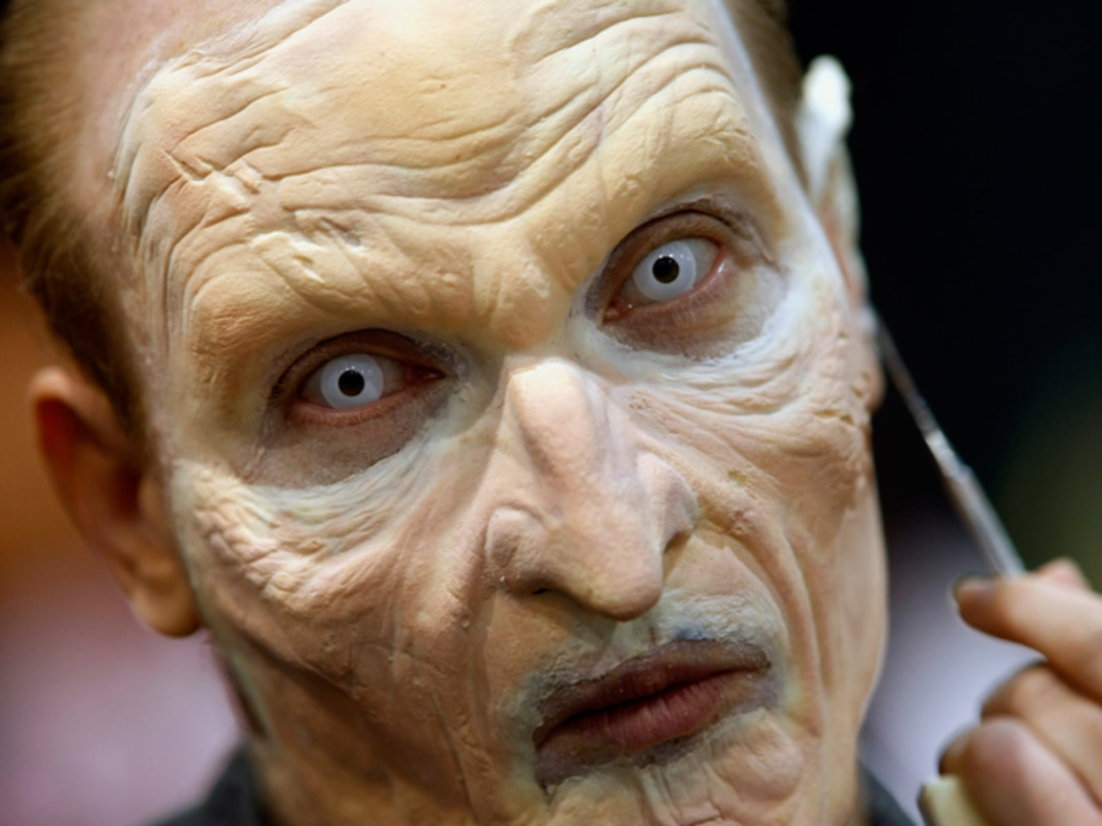 Image: A make-up artist works on a man's face while attending the 40th annual  Comic Con conference in San Diego