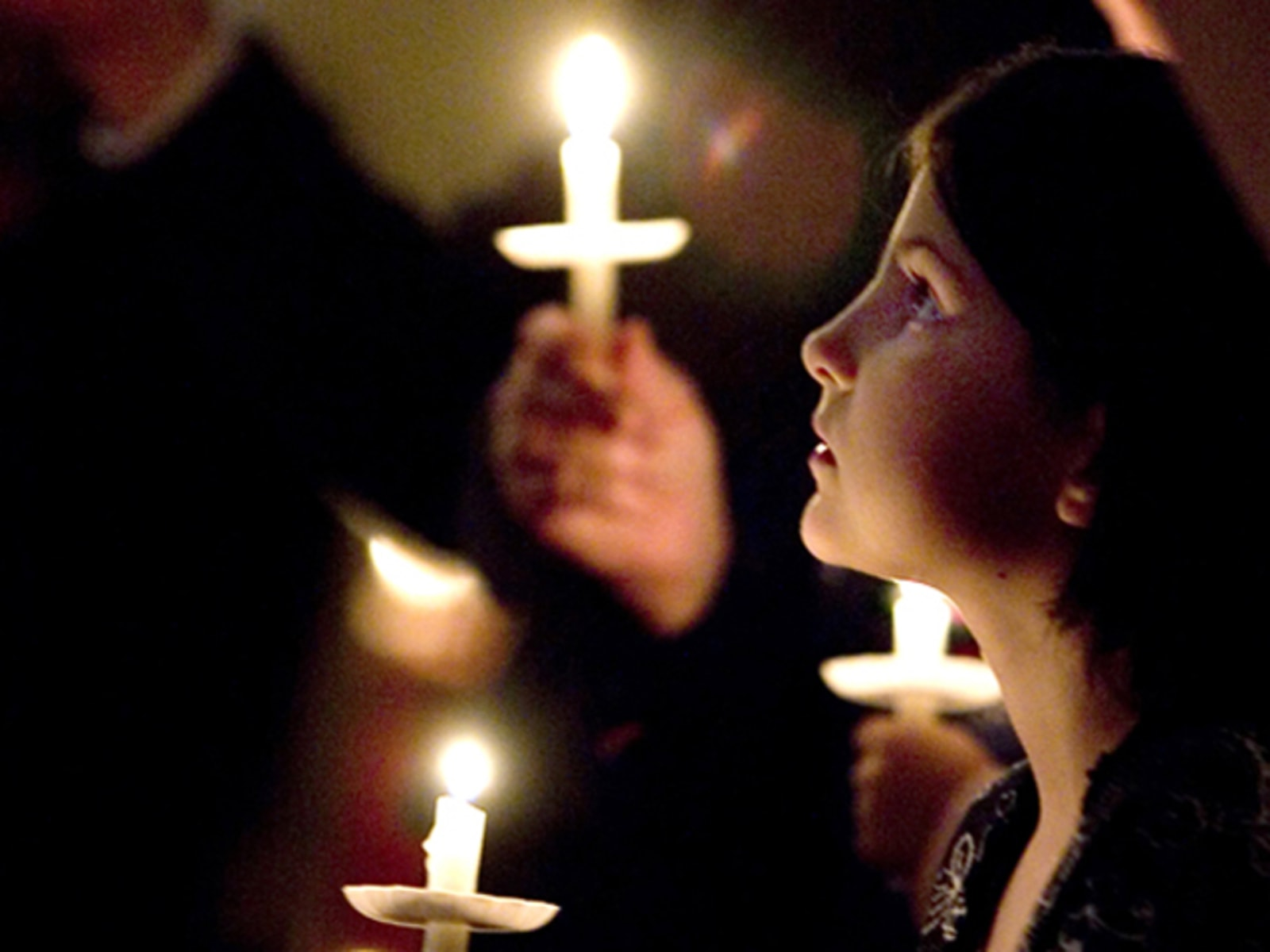 """Image: Megan Shaffer, 8, right, holds a candle during the singing of """"Silent Night"""""""