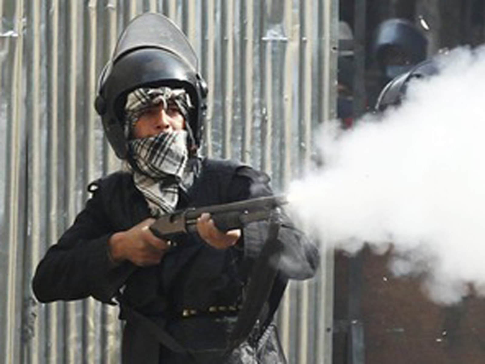 Image: A riot policeman fires a shotgun at protesters during clashes at a side street near Tahrir Square in Cairo