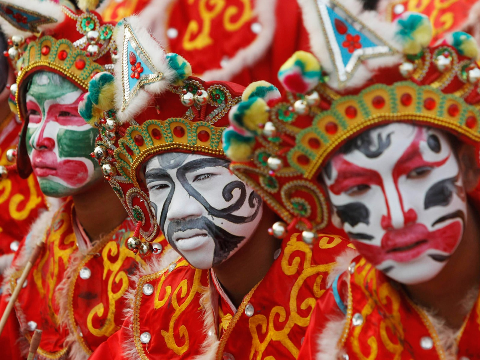 Image: Traditional Chinese dancers wait to perform ahead of the Chinese Lunar New Year celebrations in Suphan Buri province