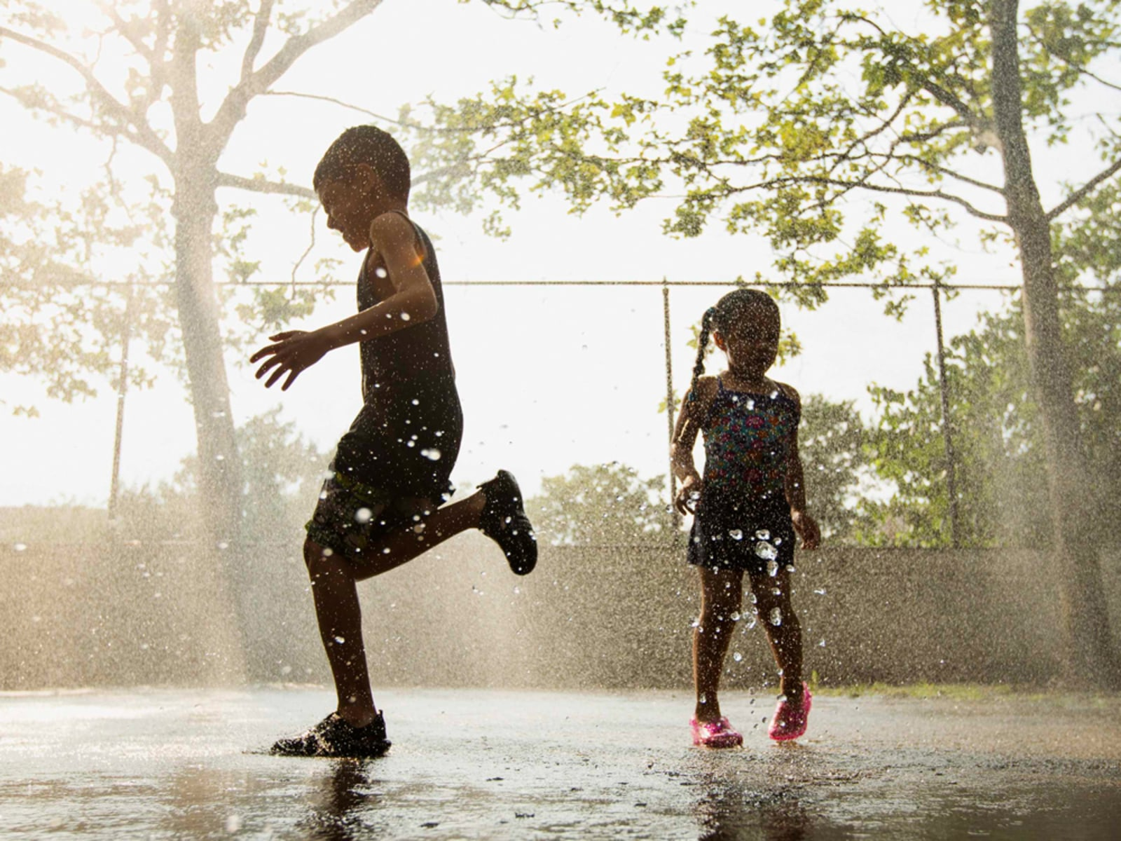 Image: Children run through a sprinkler system installed inside a playground to cool off during a hot summer day in New York
