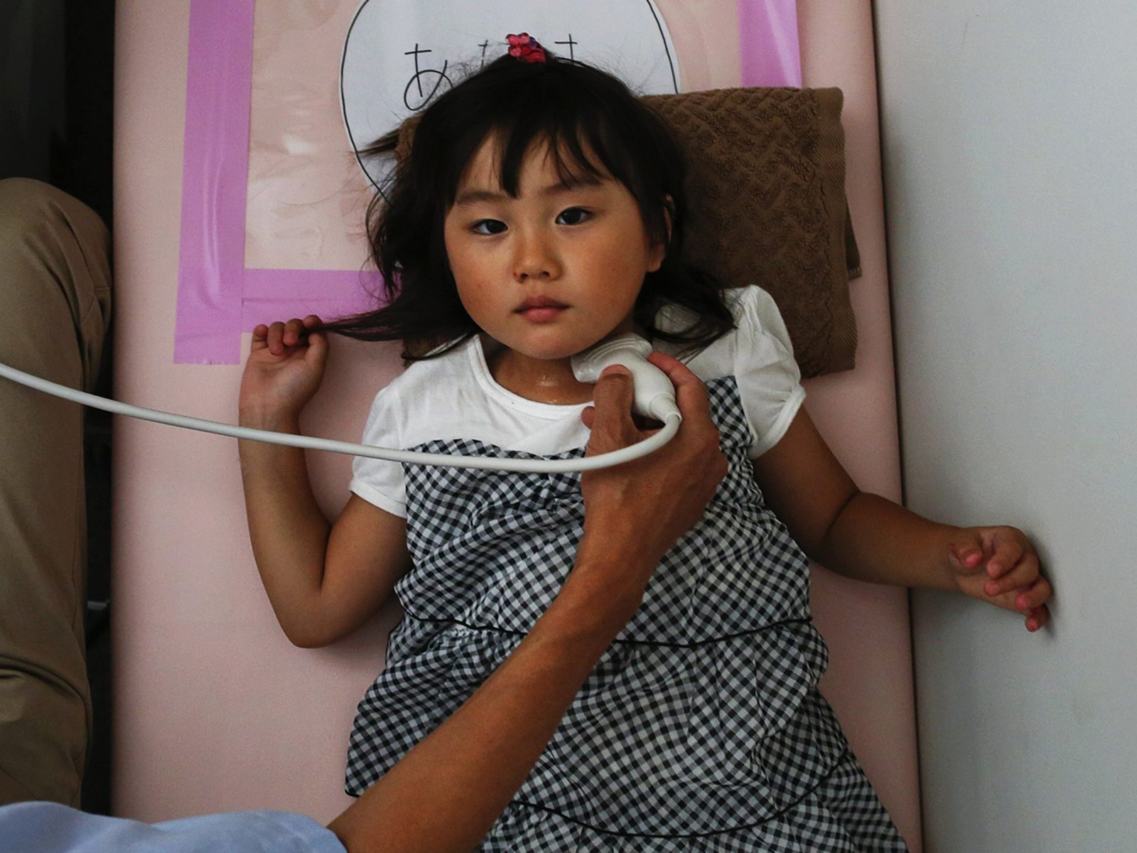 Image: A doctor conducts a thyroid examination on four year old Maria Sakamoto  brought by her mother to the office of Iwaki Radiation Citizen Centre NPO in Iwaki town