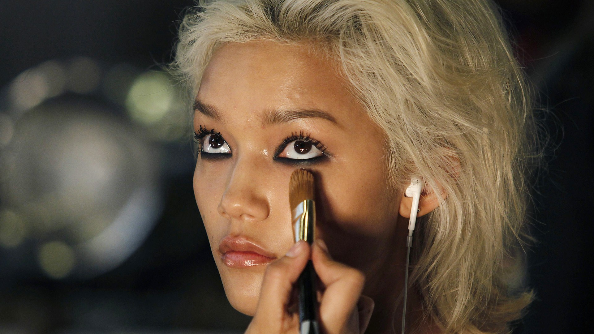 Image: A model has her make-up applied before presenting a creation by DKNY during New York Fashion Week