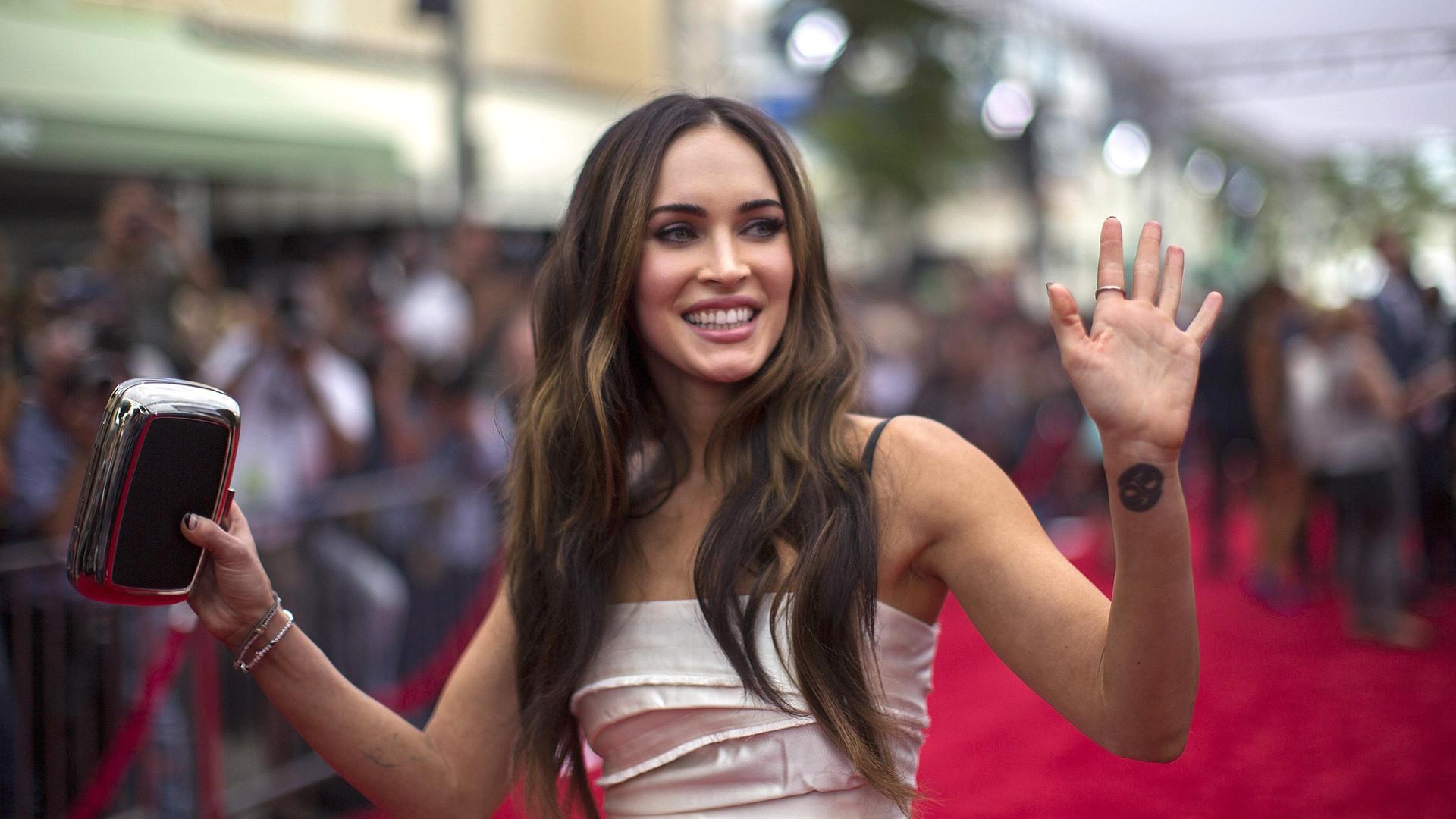 """Image: Cast member Fox waves at the premiere of """"Teenage Mutant Ninja Turtles"""" in Los Angeles"""