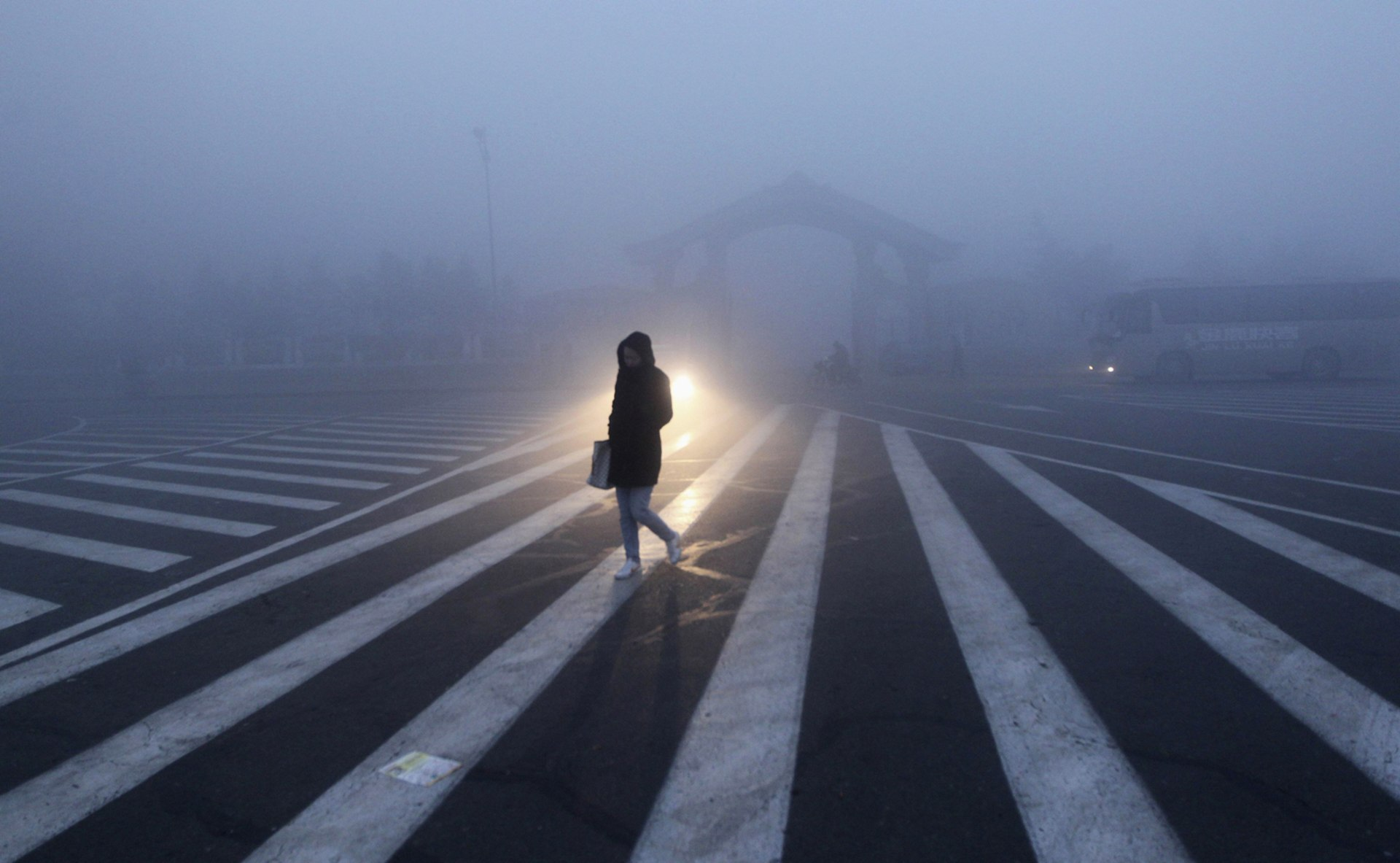Image: A woman walks along a street during a smoggy day in Changchun