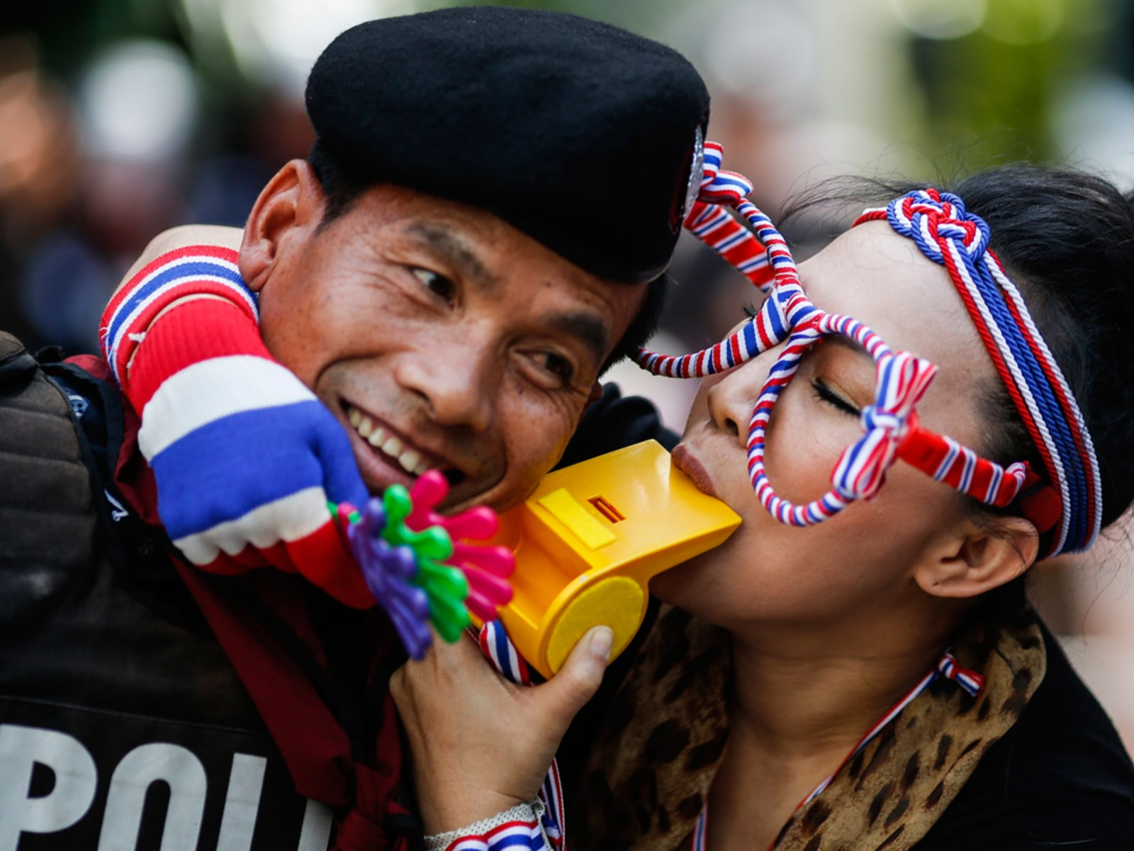 Image: An anti-government protester blows on a whistle next to a riot policeman as she gathers with others outside the headquarters of the ruling Puea Thai Party of Prime Minister Yingluck Shinawatra in Bangkok