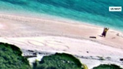 Stranded boaters rescued after writing 'SOS' in sand on deserted island
