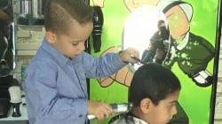 See the 4-year-old boy who cuts hair in his father's barber shop